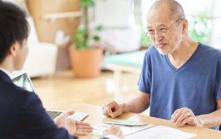 older man discusses paperwork with man in suit