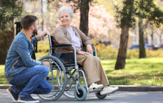 elderly parent in wheelchair visited by adult son outside