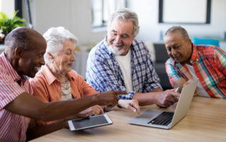 Group of happy seniors using a tablet and laptop